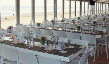 Gedekte tafels voor personeelsfeest bij feestlocatie Beachclub O in Noordwijk aan Zee.