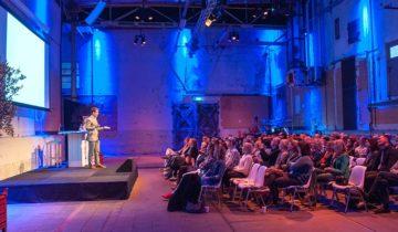 Een plenaire presentatie in loods 6 van DeFabrique feestlocatie in Utrecht.