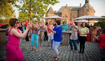 Dansende mensen op binnenplaats kasteel Ammersoyen feestlocatie in Ammerzoden.