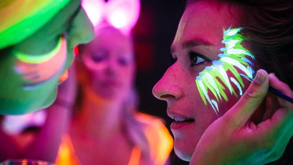 close-up van glow in the dark schmink tijdens het themafeest personeelsfeest.
