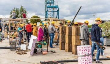 Chainreaction teambuilding mensen aan het werk om iets te bouwen met gele helmen op