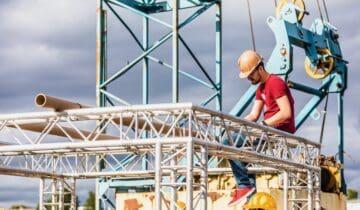 Open Up teambuilding corona Chainreaction teambuildingsactiviteit man die op een stalen buis zit
