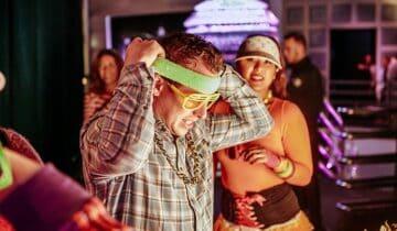 Feest der herkenning Personeelsfeest na corona Gadgetbar-Guilty-Pleasure-Party man met hoofdband en zonnebril