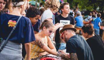 Tattoo artiest die tattoos zet op een festival